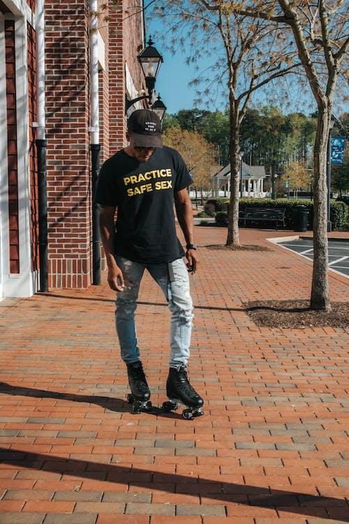 Black man practicing roller skating on sidewalk