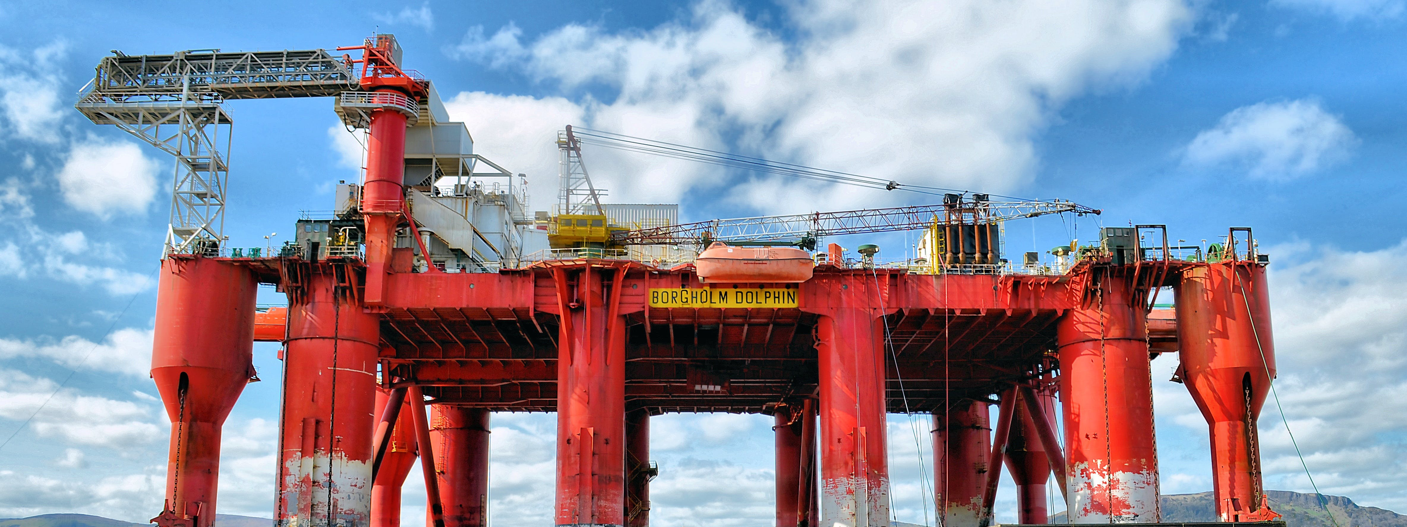 Red and Gray Oil Rig Under Blue and White Cloudy Sky