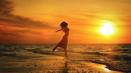 Silhouette of unrecognizable woman jumping above sea beach at sunset