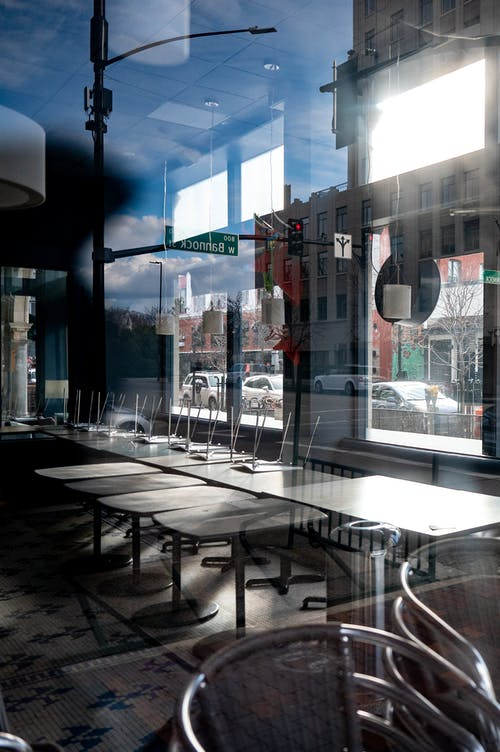 Contemporary style cafeteria interior with wooden tables and metal stools near window with shiny surface overlooking city street with building facade and parked cars in daylight