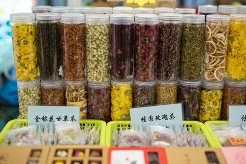 High angle of glass jars filled with assorted spices and dry fruits placed on stall in traditional Asian food market
