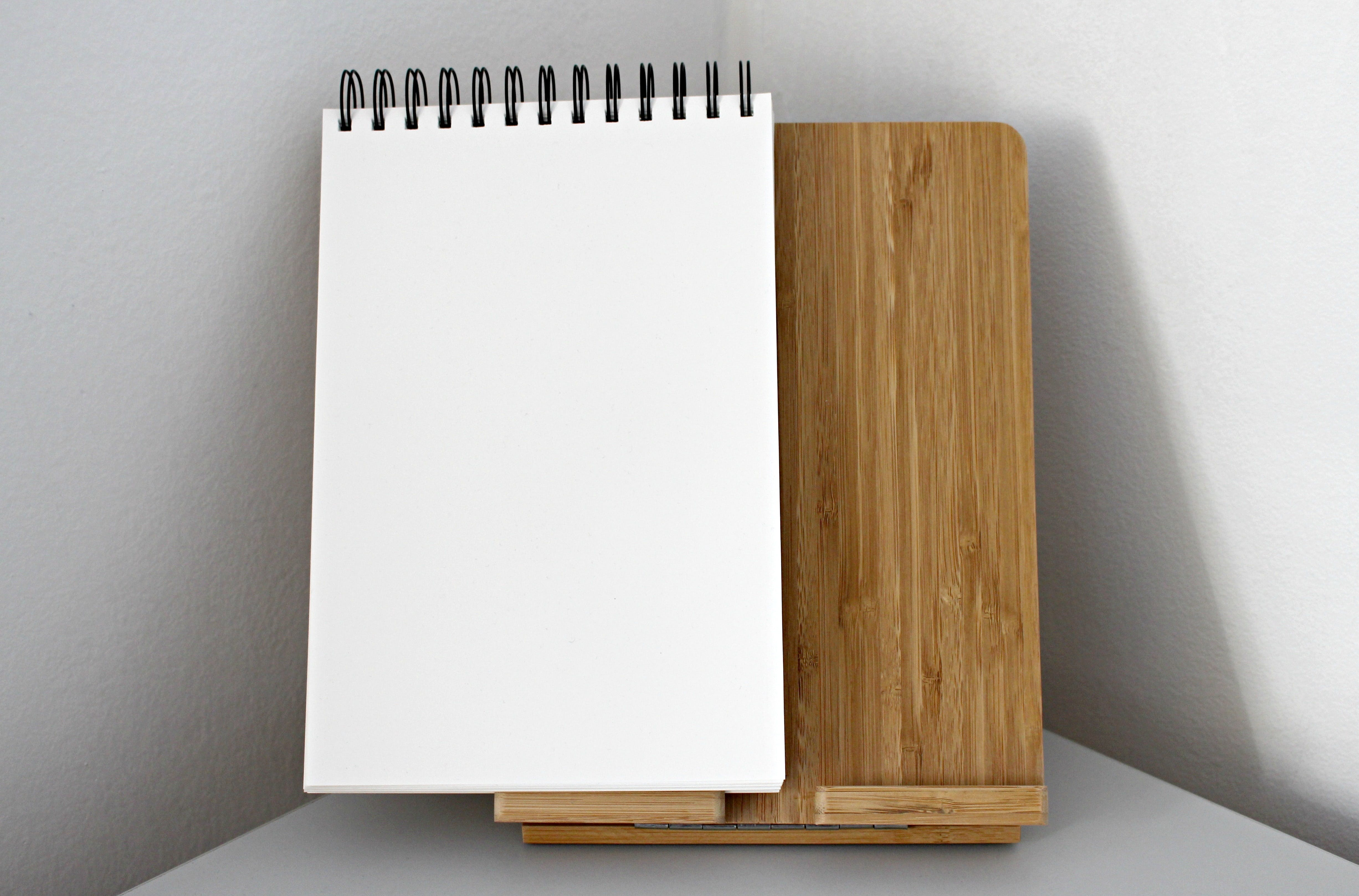White String Notebook on Top of Brown Wooden Board