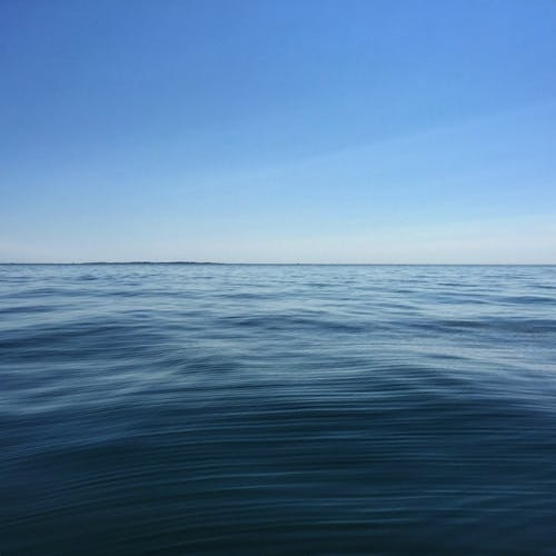 Picturesque view of endless sea with rippled water and horizon line under colorful cloudy sky in daytime