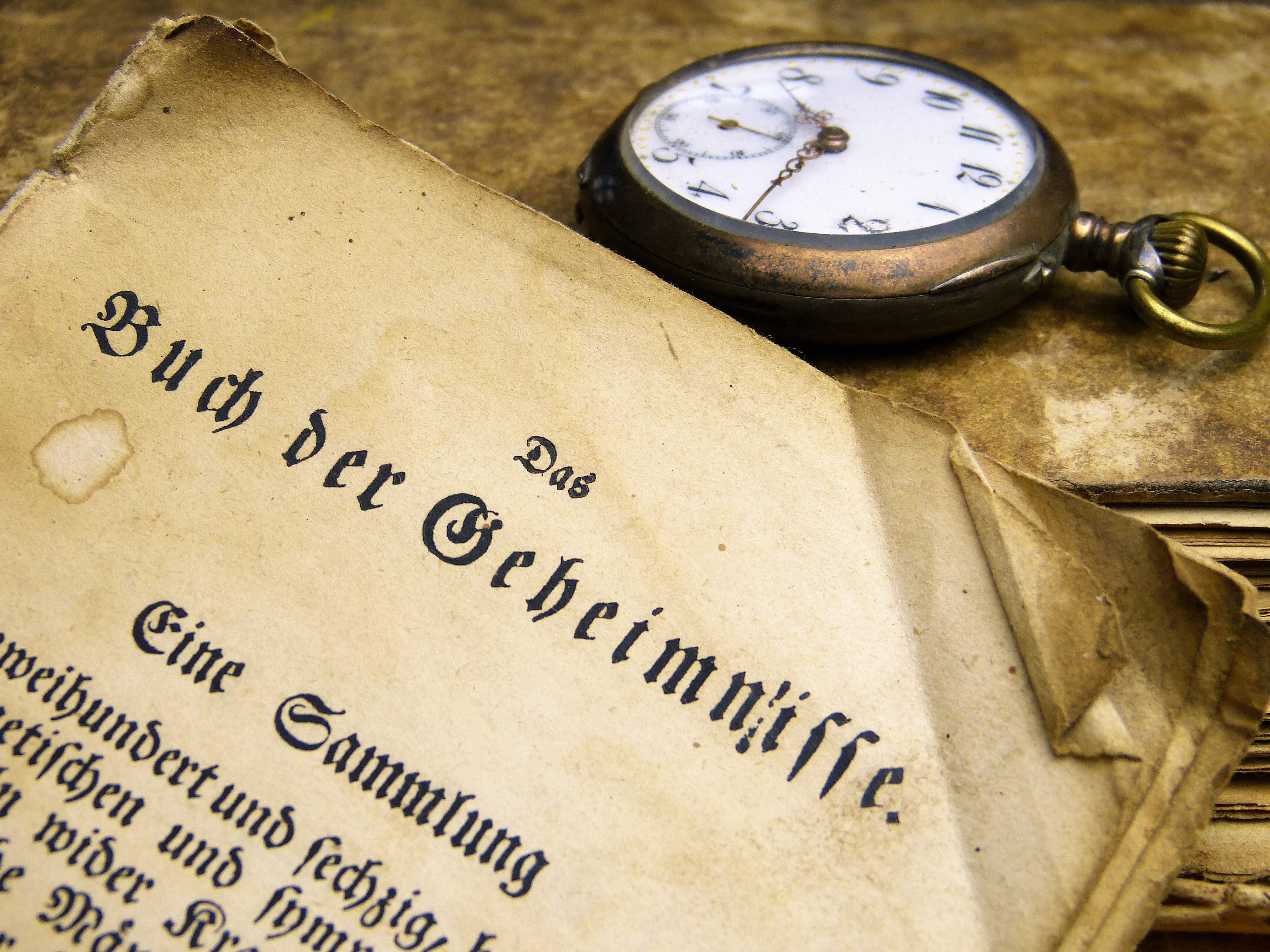 Brass-colored Pocket Watch Beside Book