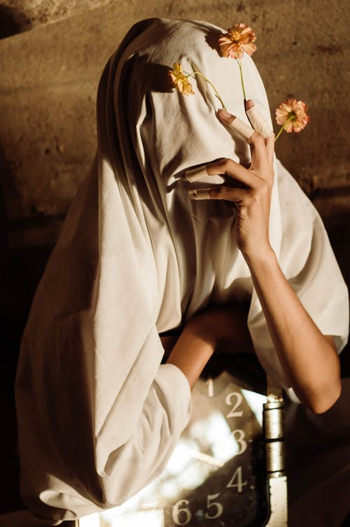 From above of anonymous female with textile cape on head and shoulders covering face with fingers in medical patches fixing bright flowers on thin stems sitting with clock
