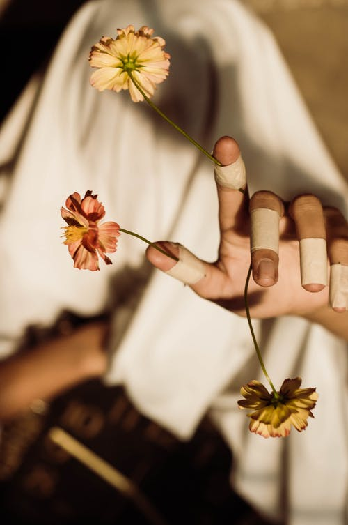 From above of crop unrecognizable lady in fabric covering face reaching arm with medical patches on fingers with bright flowers on blurred background