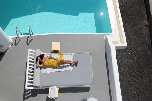 From above of unrecognizable female tourist in yellow outfit and sunglasses sunbathing on towel on sun bed near swimming pool with blue water shining in sunlight during summer trip