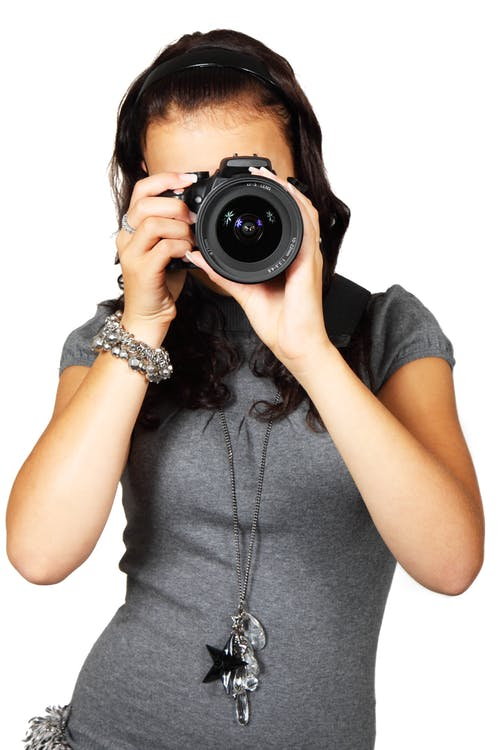 Woman in Grey T-Shirt Using Black DSLR Camera