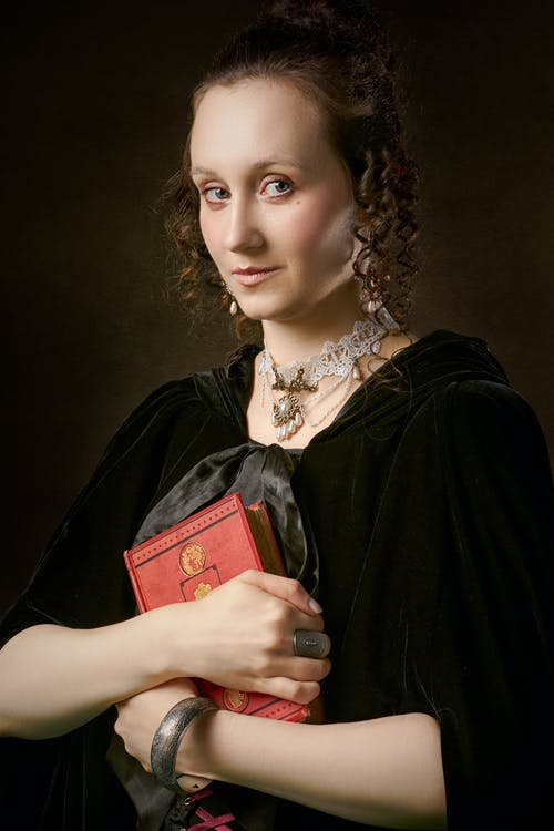 Renaissance style woman with accessories and book on black background