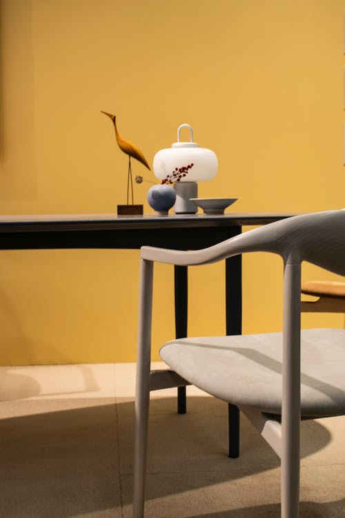 Contemporary style flat with lamp near small vase with twig and wooden statuette of bird on desk between chair and yellow wall