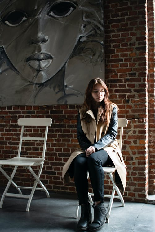 Melancholic woman on chair near brick wall with picture