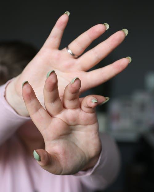 Crop woman showing hands with manicure at home