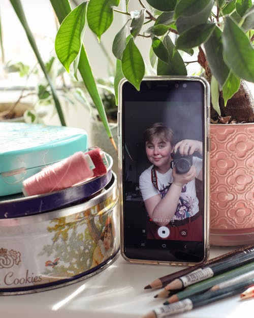 Woman shooting video on smartphone while using photo camera indoors