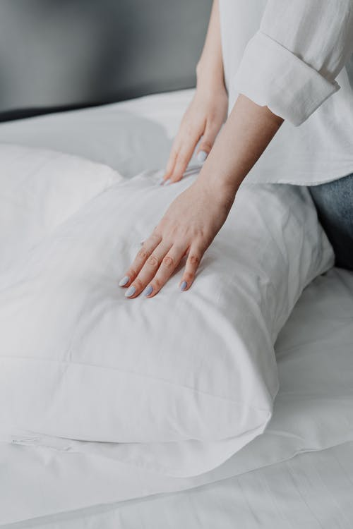 Person in White Shirt and Gray Denim Jeans Sitting on White Bed