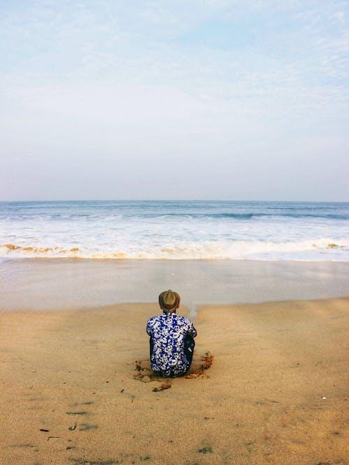 Unrecognizable traveler resting on sandy coast near ocean under sky