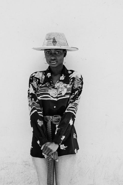 Grayscale Photo of Woman Wearing Hat and Floral Long Sleeve Shirt