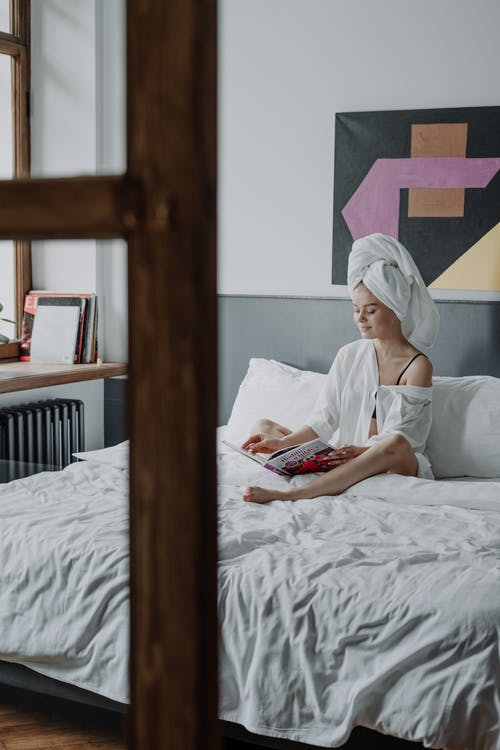 Woman in White Shirt Reading Book on Bed