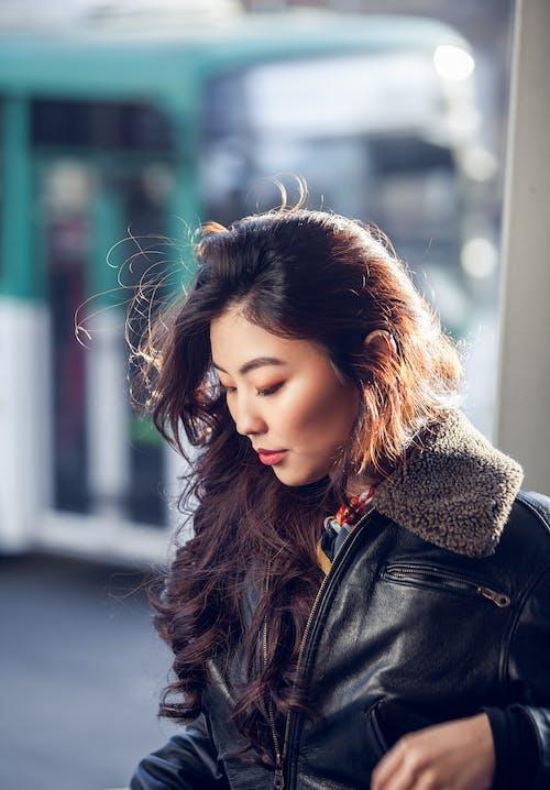 Modern ethnic woman in warm jacket on street