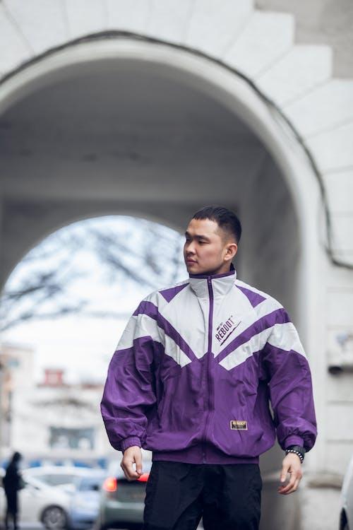 Asian man standing near arch on city street
