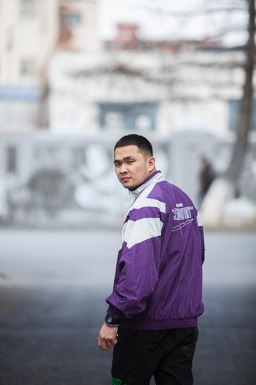 Asian man in sportswear standing on city street