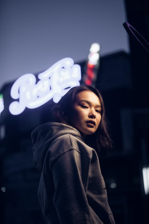 Low angle of serious Asian female standing near cafe entrance with neon sign in evening time and looking at camera