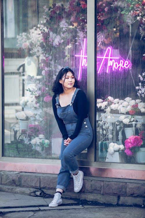 Asian woman standing near flower shop