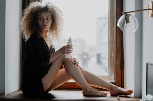 Woman in Black Dress Sitting on Brown Wooden Window
