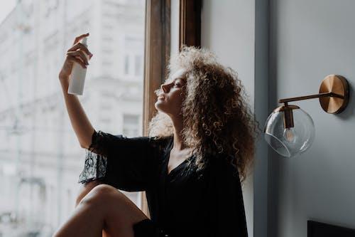 Woman in Black Dress Sitting on Window