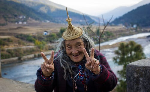 Cheerful senior ethnic female in warm clothes showing two fingers while standing in countryside and looking at camera