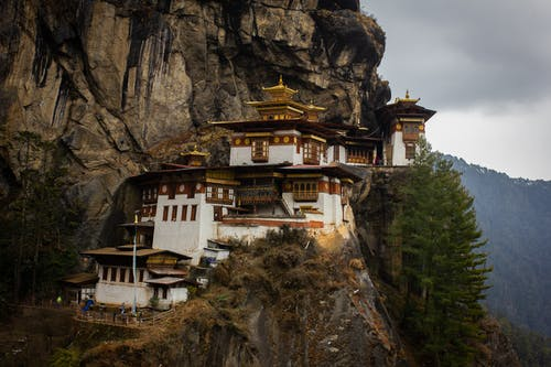 Exterior of Taktsang Lakhang monastery located on stony mountain near green trees under cloudy sky