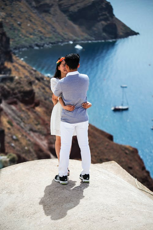 Young ethnic man and woman in casual summer clothes hugging on on concrete roof and enjoying spectacular scenery of rocky sea bay while travelling on seashore