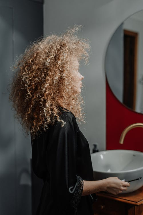 Woman in Black Jacket Standing Near Round Mirror