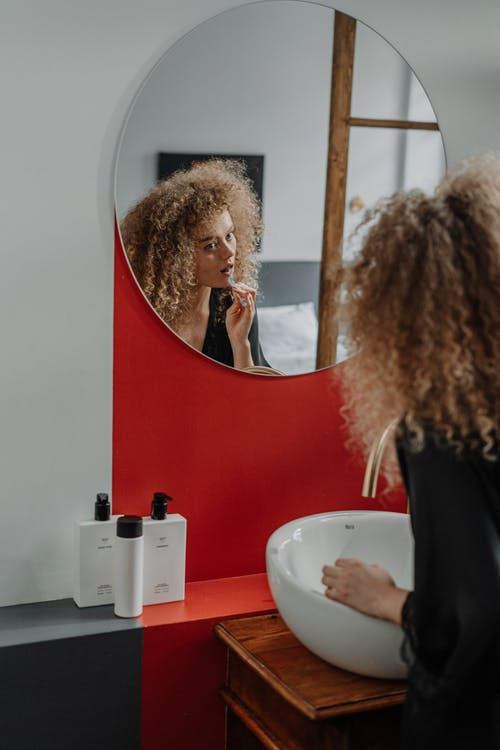 Woman in Black Long Sleeve Shirt Standing in Front of Mirror