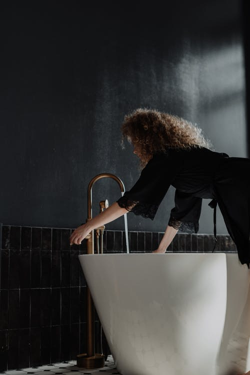 Woman in Black Long Sleeve Shirt and Blue Denim Jeans Standing on Bathtub