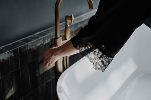 Person in Black and White Skirt Standing on White Bathtub