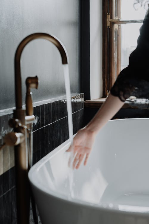 Person in Black T-shirt Washing Hand on Bathtub