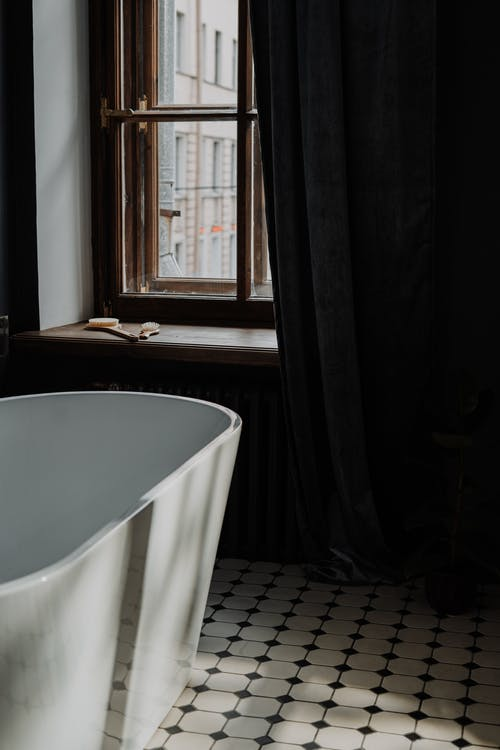 White Bathtub Near Black Window Curtain