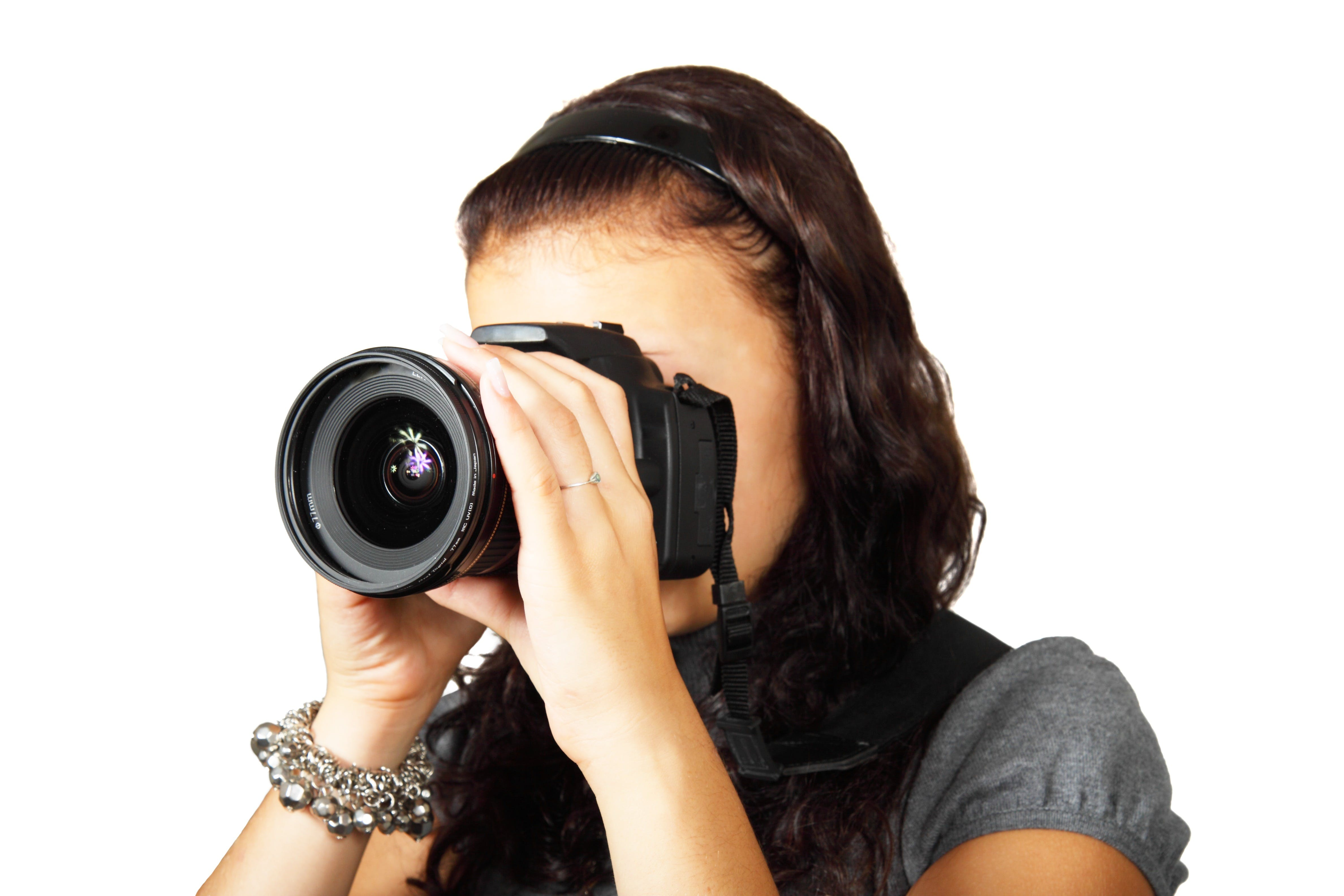 Woman in Grey Shirt Taking Picture With Dslr Camera