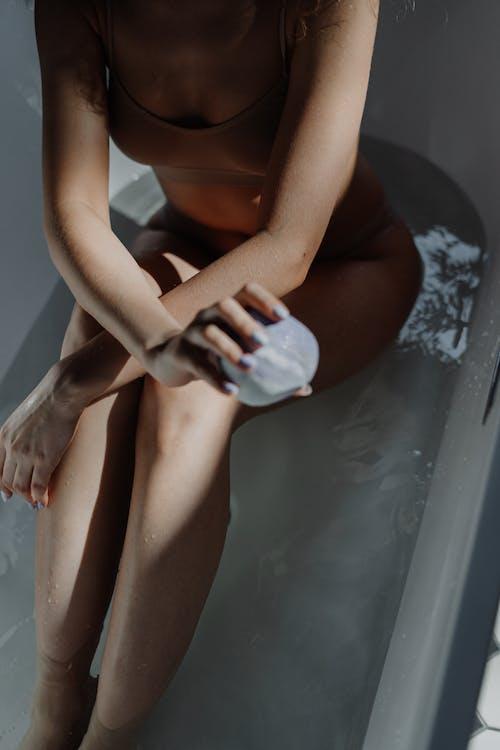 Woman in Brown Bikini Sitting on White Ceramic Bathtub