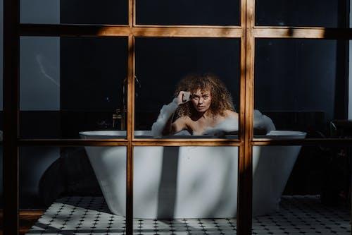 Woman in Black Long Sleeve Shirt Sitting on Bathtub