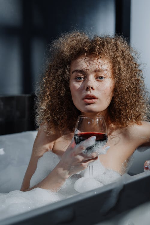 Woman in White Bath Tub Holding Clear Drinking Glass