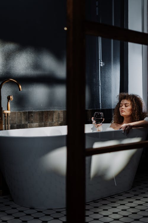 Woman in Bathtub Holding a Cup of Water
