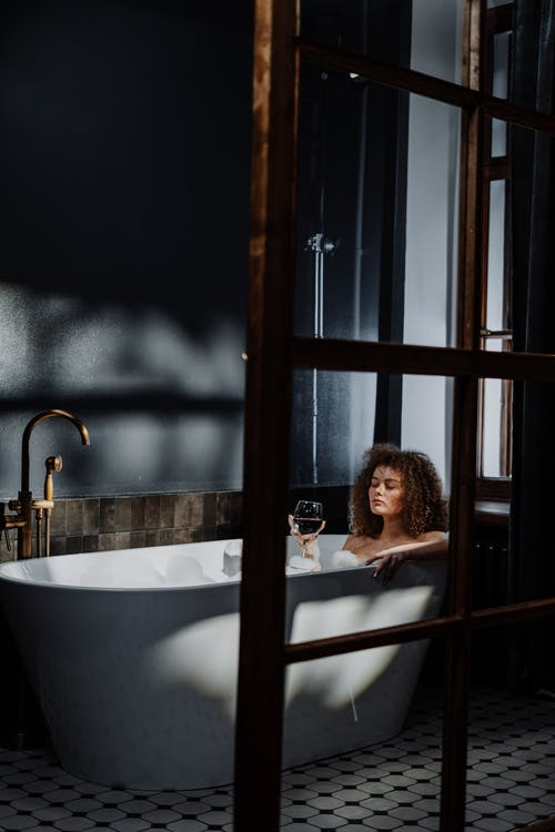 Woman in Bathtub Near Window