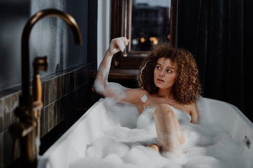 Topless Girl in Bathtub With Bubbles