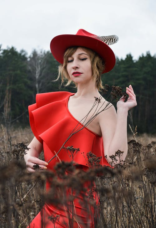 Gorgeous young lady wearing classy red evening dress and stylish hat standing gracefully on grassy field in nature during overcast day