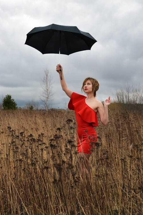 Full length gorgeous young lady wearing classy red gown standing on grassy lawn with umbrella in raised hand during overcast rainy day