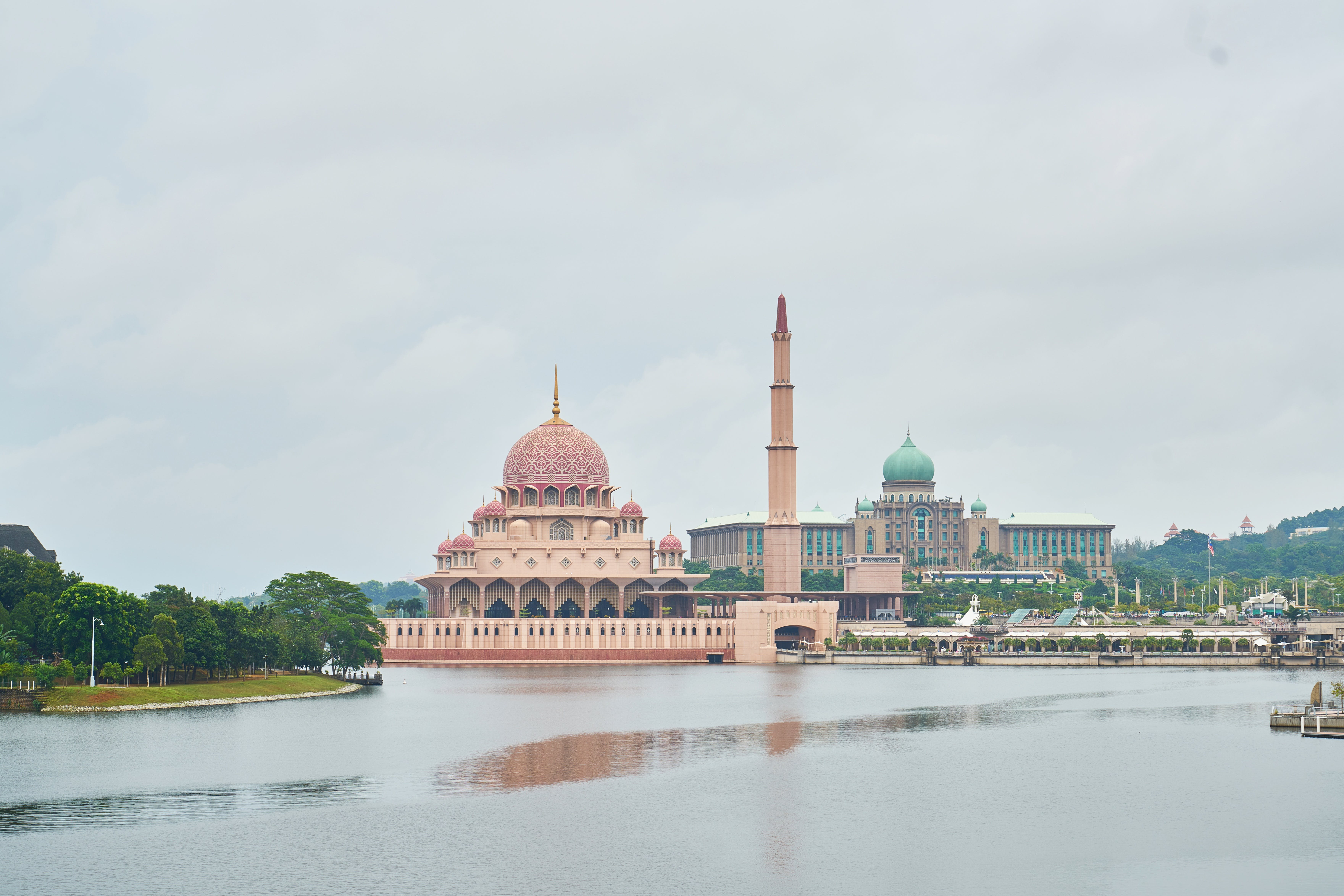 Brown Mosque Beside Tower Near Body of Water
