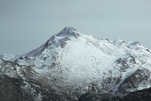 Dramatic view of majestic mountain summit under snow