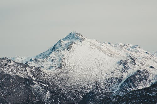 Severe scenery of majestic mountains covered with thick layer of snow against gray overcast sky