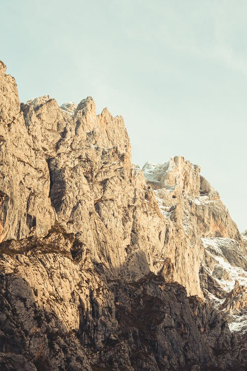 Amazing view of rocky cliffs of high mountains located against cloudy sky in sunny day